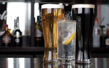 Alcoholic and soft drinks (Beer, Guiness and Lemonade) on a bar.  Image is used to support the hospitality sector in the UK.